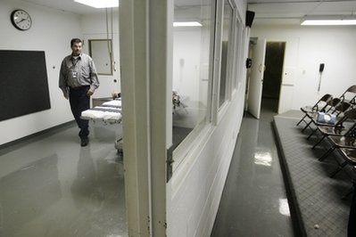 Terry Crenshaw, wardens assistant at the Oklahoma State Penitentiary, walks past the gurney in the e