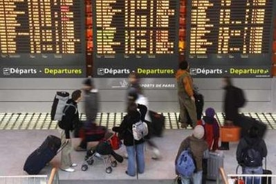 Passengers look at a flight departure information board in a terminal at the Charles-de-Gaulle airpo