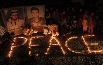 Indians light lamps near portraits of soldiers who were killed in the 2008 Mumbai terror attacks
