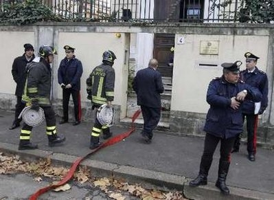 Fire-fighters carrying hoses enter the Greek embassy in Rome