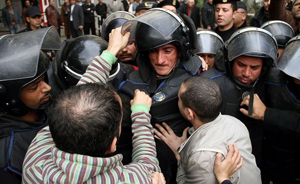 Egyptian demonstrators harass a soldier during a protest in front of the Tunisian embassy in Cairo, Egypt