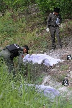 Thai police inspect dead bodies