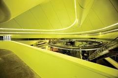 حدید در این فضا یک پل هوایی درست کرده. روی قسمتی از پل که از زمین جدا میشود و با سطحی شیبدار بالا میرود، اتومبیلها قرار دارند و روی قسمتی از آن که بهشکل دایره در مرکز فضا قرار دارد، دوچرخهها. در پسزمینۀ این فضای جذاب، فضای پر از قوسهای سهبُعدی خود ساختمان دیده میشود. حدید بین زیباییهای ساختمان و فضای نمایش وسایل نقلیه، بهخوبی ارتباط برقرار کرده.