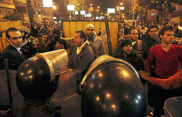 Anti-Mursi protesters scuffle with riot police during clashes with supporters of Egyptian President Mohammed Mursi, near the presidential palace in Cairo, December 5, 2012