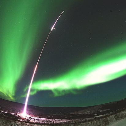 موشک دو مرحلهای را در میان آسمانی که به نور سبز رنگ شفق قطبی آلاسکا