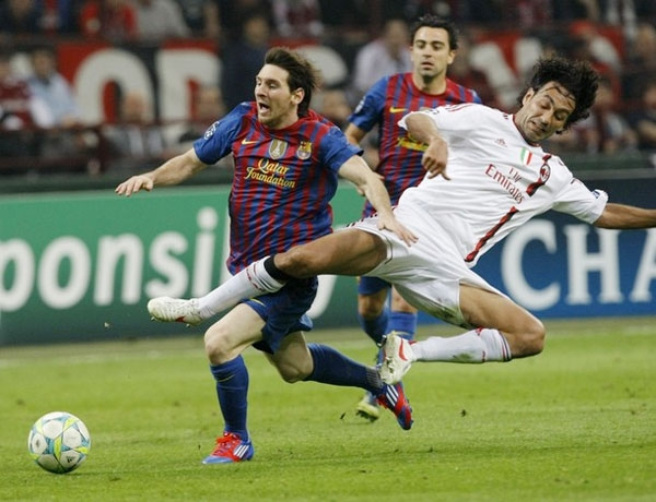 Barcelona's Lionel Messi (L) is challenged by AC Milan's Alessandro Nesta during their UEFA Champions League quarter final first leg soccer match at the San Siro stadium in Milan March, 28 2012.