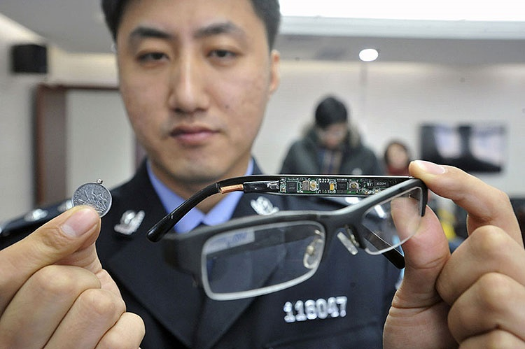 A police officer displays a pair of glasses with a hidden camera and a tiny receiver attached to a coin, equipment used to cheat on exams, confiscated by the police in Shenyang, Liaoning province, China