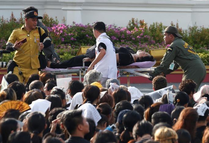 کارکنان بهداشتی به تایلندیهای سوگوار کمک میکنند