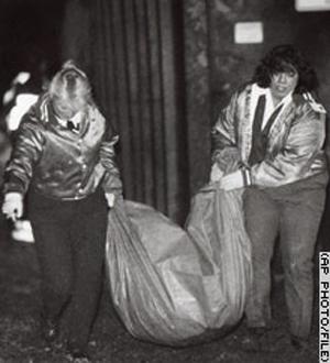 خدمه آمبولانس جنازهها را از محل جنایت خارج میکنند