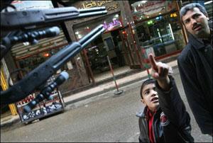 یکی از آخرین عکسهای رازوری: کودک فلسطینی یک نظامی صهیونیست را به پدر خود نشان میدهد