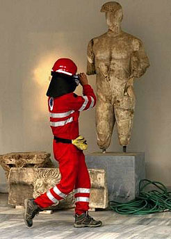 A Greek firefighter takes photos of an ancient Greek statue on the yard of the archaeological museum in Ancient Olympia