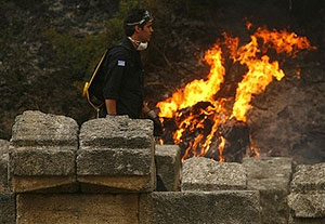 A firefighter passes next ancient pieces of columns as the fire burns at Olympia