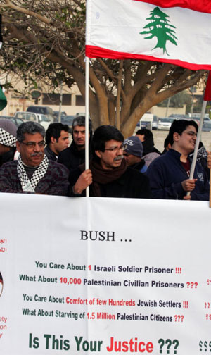 Demonstrators, carrying a Lebanese flag, protest outside the US Embassy in Manama 12 January 2008 against US President George W. Bush's visit to Bahrain