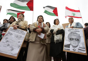Women, carrying anti-Bush placards protest outside the US Embassy in Manama