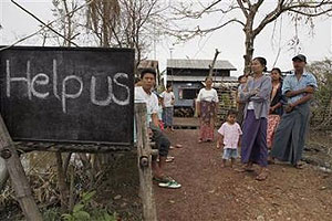 Villagers display a sign saying 'Help Us' on a road near Kundangon, Myanmar
