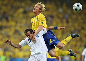 Greece's Fanis Gekas, and Sweden's Petter Hansson challenge for the ball