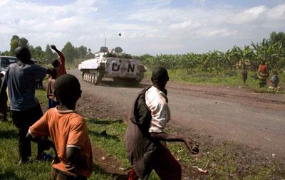 People throw stones at UN peacekeepers patrolling on a road in Kibati