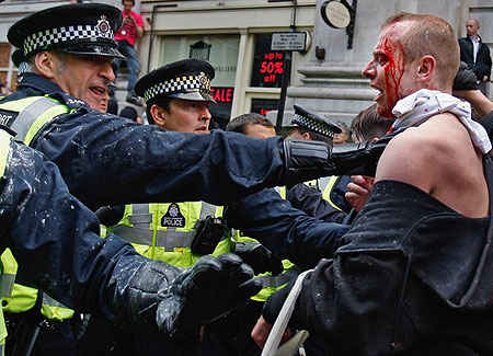A bleeding protester is held back by police as Anti capitalist and climate change activists demonstrate in the City of London on April 1, 2009