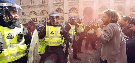Policemen (L) clash with protestors outside the Bank of England in London