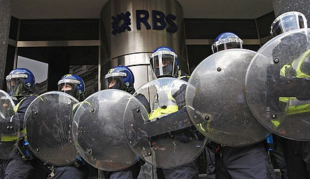 Police in riot gear stand outside a Royal bank of Scotland branch near the Bank of England in London April 1, 2009.