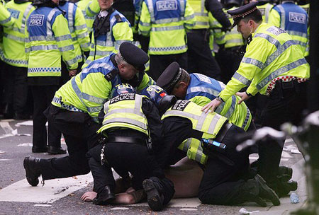 A climate change and anti-capitalist activist is detained by police during a demonstration outside a branch of the Royal Bank of Scotland (RBS) on April 1, 2009 in London, England.