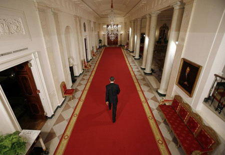 U.S. President Barack Obama walks down the White House Cross Hall from the East Room following a nationally-televised news conference in Washington, March 24, 2009