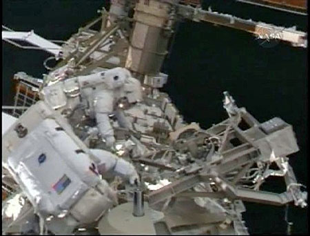 Space shuttle Discovery astronauts Joseph Acaba (foreground) and Richard Arnold work outside the International Space Station in this image from NASA TV March 23, 2009.