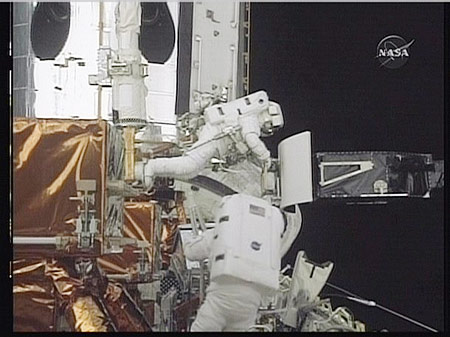 In this May 14, 2009 image taken from NASA video, astronaut John Grunsfeld (top) makes a repair with colleague Drew Feustel during the first space walk to repair the Hubble space telescope.