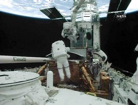 Spacewalker John Grunsfeld (L) prepares the old Wide Field Planetary Camera for storage in Atlantis's payload bay as Drew Feustel (top), attached to the robot arm, looks on in this image from NASA TV May 14, 2009.