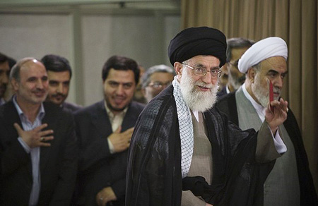 Iran's Supreme Leader Ayatollah Ali Khamenei leaves the polling station with an identification card in hand after casting his ballot in the Iranian presidential election in Tehran June 12, 2009.