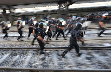 Riot policemen run after protesters who stand on a track of Termini station during a protest against the upcoming G8 summit on July 7, 2009 in Rome. Italian police made around 40 arrests Tuesday as protests against the upcoming G8 summit opening on July 8 saw demonstrators hurl bottles and set fire to tyres on the streets of Rome, officials and witnesses said.