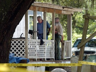 Glynn County investigators work on the porch of the house at the New Hope Plantation mobile home park in Brunswick, Ga., where seven people were found slain Saturday morning, Aug. 29, 2009