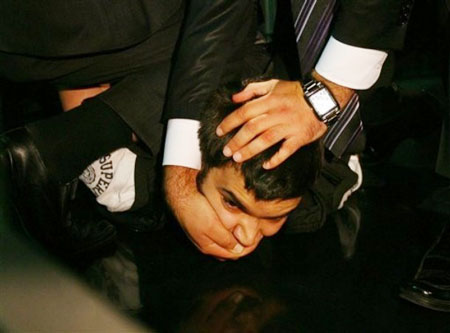 Security guards detain Selcuk Ozbek, a student journalist who threw a shoe at Dominique Strauss-Kahn, the Managing Director of the International Monetary Fund, the IMF, as he was addressing students at the Bilgi University in Istanbul, Turkey, Thursday, Oct. 1, 2009.