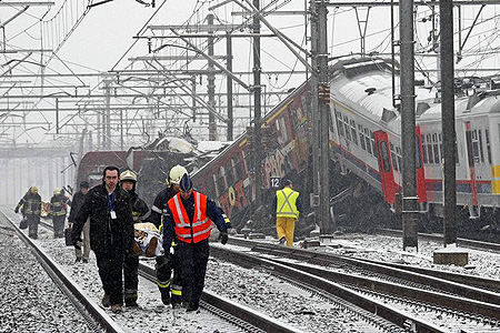 Emergency workers carry the victim of a train crash on a stretcher at the site of the crash near Halle February 15, 2010. Two trains crashed head-on outside Brussels on Monday, killing at least 20 people, officials and Belgian broadcaster VRT said