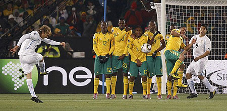 Uruguay's Diego Forlan (L) takes a free kick during a 2010 World Cup Group A soccer match against South Africa at Loftus Versfeld stadium in Pretoria June 16, 2010.