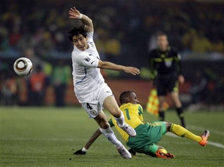 Uruguay's Jorge Fucile, left, goes for the ball during the World Cup group A soccer match between South Africa and Uruguay at the Loftus Versfeld Stadium in Pretoria, South Africa, Wednesday, June 16, 2010