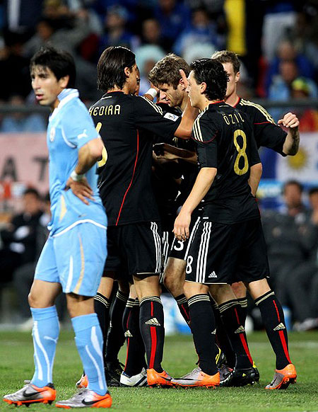 PORT ELIZABETH, SOUTH AFRICA - JULY 10: Team mates celebrate with Thomas Mueller of Germany after he scores the opening goal during the 2010 FIFA World Cup South Africa Third Place Play-off match between Uruguay and Germany at The Nelson Mandela Bay Stadium on July 10, 2010 in Port Elizabeth, South Africa