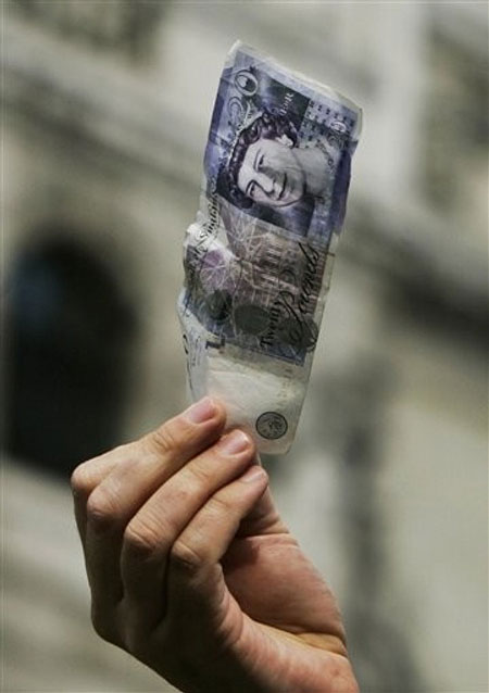 Ahead of the G20 summit, a lone protester holds up a banknote of 20 British pounds as he delivers a speech on the financial issues, in central London's City financial district, Tuesday March 31, 2009.